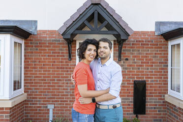 Portrait of happy couple in front of their new home - WPEF01967