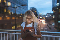 Young woman in the city at dusk looking at her smartphone - WPEF01970