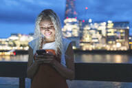 Young woman in the city at dusk looking at her smartphone - WPEF01979