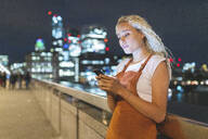 Young woman in London at night looking at her smartphone - WPEF01985
