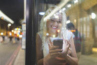 Young woman in London at night looking at her smartphone and waiting for the bus - WPEF01988