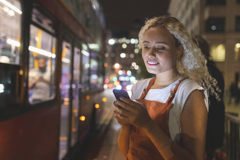 Young woman in London at night looking at her smartphone, bus in the background - WPEF01991