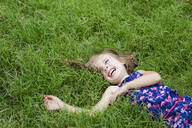 Laughing little girl lying on a meadow in summer - XCF00252