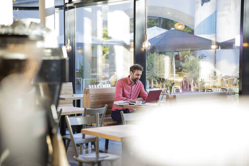 Young man using laptop in a cafe - FKF03625
