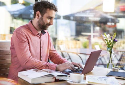 Young man using laptop in a cafe - FKF03628