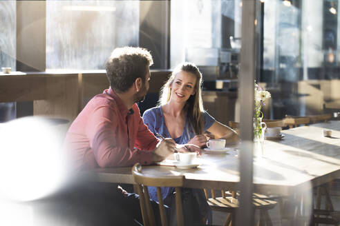 Woman and man talking at table in a cafe - FKF03631