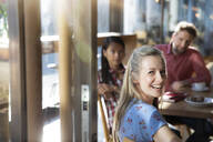 Portrait of happy woman with friends in a cafe - FKF03643