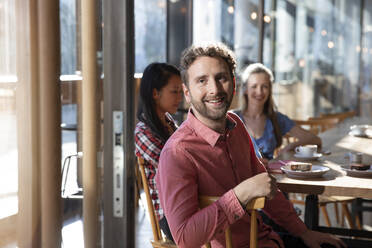 Portrait of smiling man with friends in a cafe - FKF03646