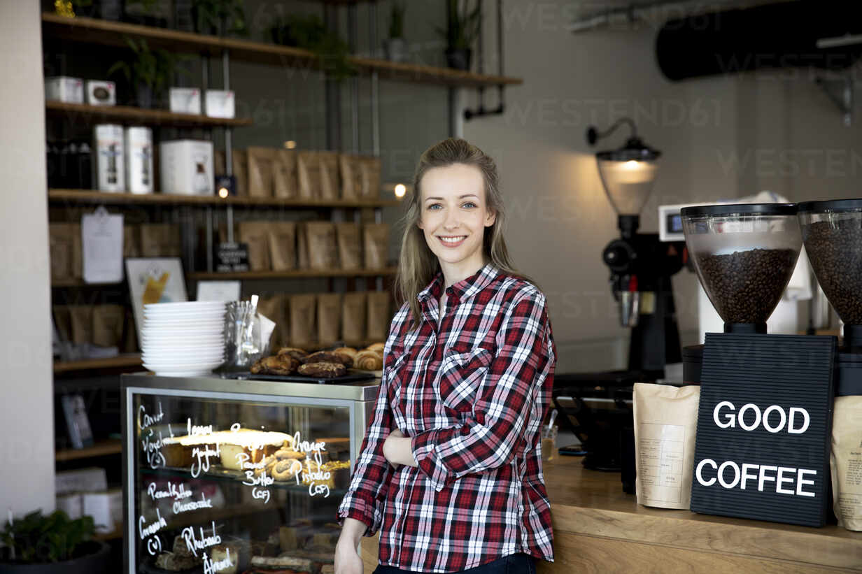 Portrait of smiling woman at the counter of a cafe - FKF03655 - Florian Küttler/Westend61