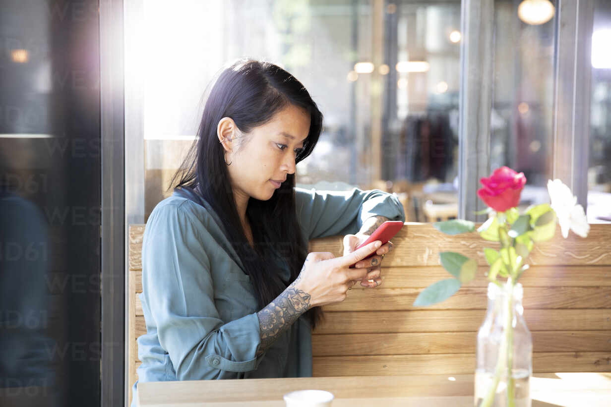 Woman using cell phone in a cafe - FKF03658 - Florian Küttler/Westend61