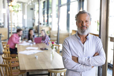 Portrait of mature businessman in a cafe with colleagues having a meeting in background - FKF03673