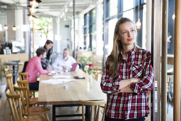 Portrait of casual businesswoman in a cafe with colleagues having a meeting in background - FKF03676