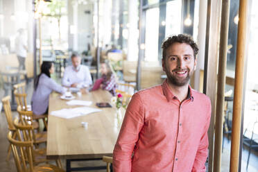 Portrait of casual businessman in a cafe with colleagues having a meeting in background - FKF03682