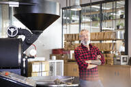 Portrait of confident mature man in a coffee roastery - FKF03697