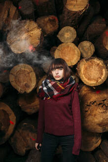 Portrait of young woman at stack of wood - DAMF00117