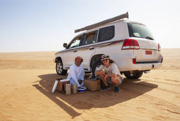 Tourist having a coffee break with his local driver in the desert, Wahiba Sands, Oman - WWF05287