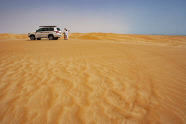 Tourist talking to his driver in the desert next to off-road vehicle, Wahiba Sands, Oman - WWF05296