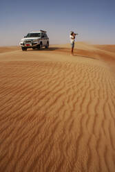 Man taking pictures in the desert, next to off-road vehicle,  Wahiba Sands, Oman - WWF05311