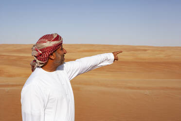 Bedouin in National dress standing in the desert, pointing at distance, Wahiba Sands, Oman - WWF05314