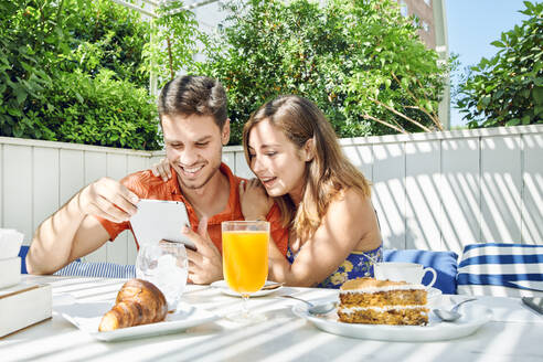 Cheerful young couple using tablet during breakfast - JNDF00109