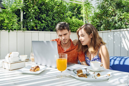 Young couple using laptop during breakfast - JNDF00112