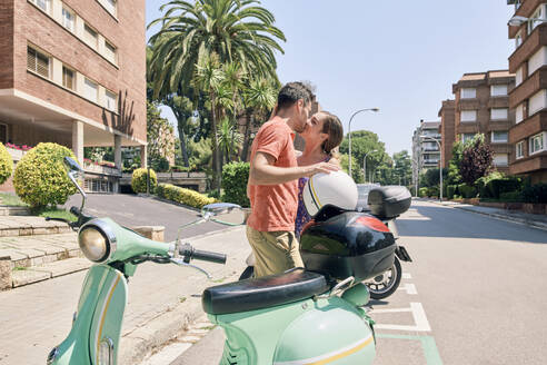 Young couple kissing at a vintage motor scooter - JNDF00115