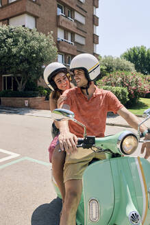 Young couple on a vintage motor scooter - JNDF00118
