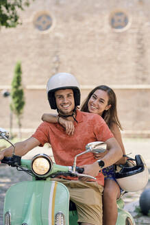 Portrait of a smiling young couple on a vintage motor scooter - JNDF00124