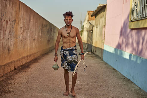 Tribal man with his traditional arch and arrows walking in an alley, Lubango, Angola - VEGF00755