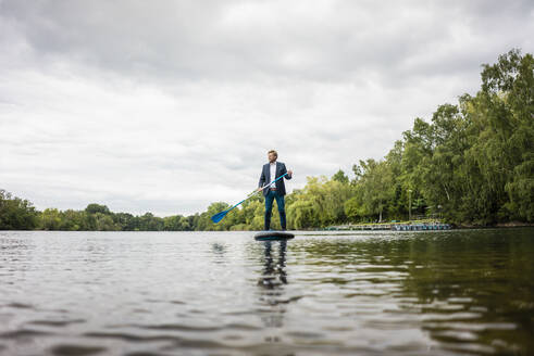 Businessman stand up paddling on a lake - JOSF03781