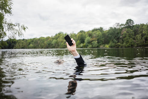 Businessman's hand holding cell phone inside a lake - JOSF03784
