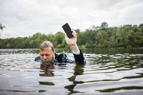 Businessman holding cell phone inside a lake - JOSF03787