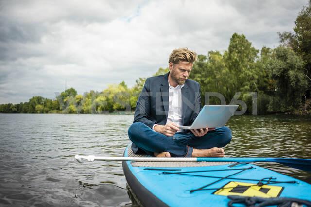 Businessman sitting on SUP board on a lake using laptop - JOSF03790 - Joseffson/Westend61