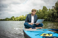 Businessman sitting on SUP board on a lake using laptop - JOSF03790
