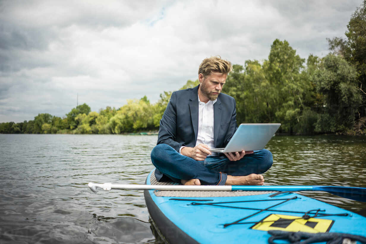 Businessman sitting on SUP board on a lake using laptop - JOSF03790 - Joseffson/Westend61