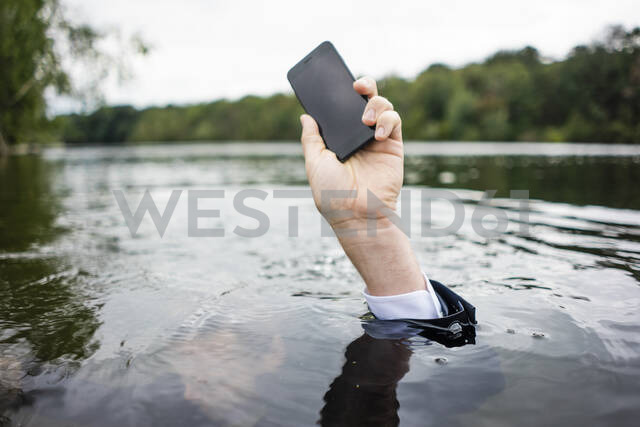 Businessman's hand holding cell phone inside a lake - JOSF03799 - Joseffson/Westend61