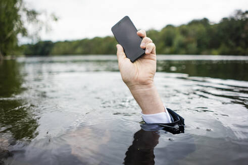 Businessman's hand holding cell phone inside a lake - JOSF03799