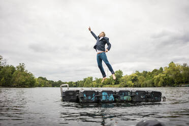 Businessman jumping on platform in a lake - JOSF03802