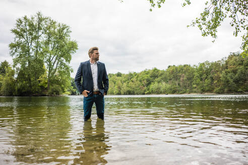 Businessman standing in a lake looking out - JOSF03808