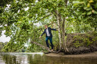 Businessman balancing on tree trunk over a lake - JOSF03811