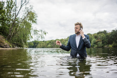 Businessman standing in a lake talking on the phone - JOSF03817