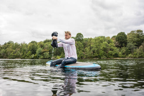 Wet businessman sitting on SUP board on a lake - JOSF03820