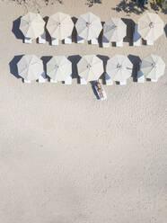 Woman lying on sun lounger at the beach, Gili Air, Gili Islands, Indonesia - KNTF03586