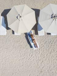 Woman lying on sun lounger at the beach, Gili Air, Gili Islands, Indonesia - KNTF03589