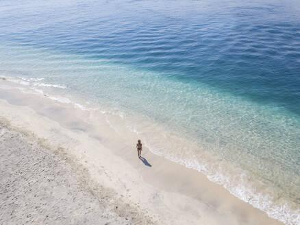 Woman walking on the beach, Gili Air, Gili Islands, Indonesia - KNTF03592