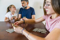 Father with two daughters playing cards on wooden table at home - MGIF00701