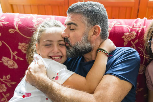 Father hugging with daughter on couch at home - MGIF00707