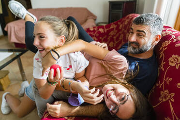 Father with two playful daughters on couch at home - MGIF00710