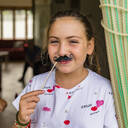Portrait of smiling girl with toy moustache - MGIF00716