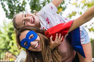 Two happy sisters with eye mask playing in garden - MGIF00725